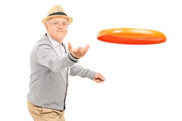 Senior man throwing a Frisbee disk
