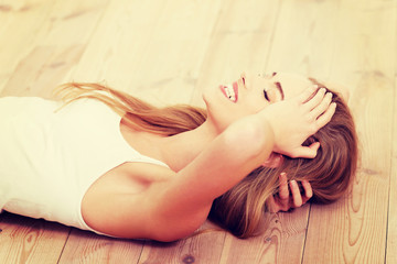 Beautiful carefree young casual woman lying on the floor.