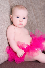 funny baby girl in pink skirt sitting