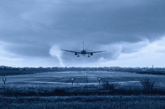 airplane landing on the runway with rain