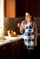 housewife looking at orange on country styled kitchen