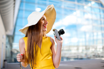 Young traveling woman with photo camera and panama dressed in ye