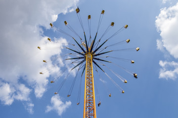 Volksfest hohes Kettenkarussell unter blauem himmel