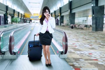 Businesswoman making a phone call at airport