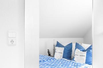 Schlafzimmer Bett mit blauen Kissen