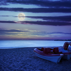 calm sea beach with boats at night