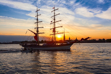 Sailing ship against Peter and Paul fort in rays of setting sun