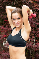 Attractive Woman lifts barbells overhead during outdoor workout