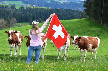 Girl with the Swiss flag against cows. Emmental, Switzerland