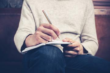 Man on sofa taking notes