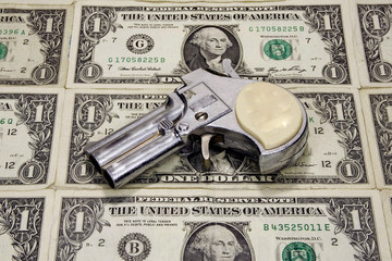 Toy revolver on a sheet on one dollar bills.