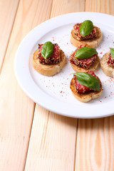 Tasty canapes with salami  and basil leaves,