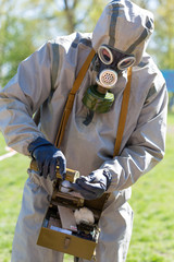 Human in protective suit and gas mask making analyzes