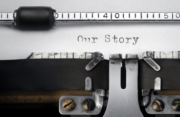 """""""Our Story"""" written on an old typewriter"""
