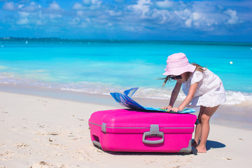 Little adorable girl with big colorful suitcase and a map in