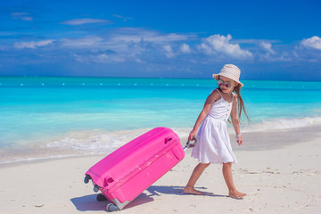 Little adorable girl with big colorful suitcase in hands walking