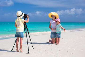 Little cute girl making photo of her family at tropical beach