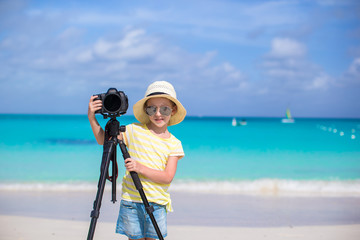 Portrait of little girl with camera on a tripod at white sandy