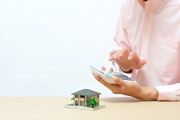 家の模型を使ってプレゼンテーションをするビジネスマン