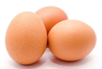Three brown chicken eggs isolated on a white background