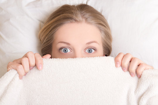 funny young woman lying in bed under blanket