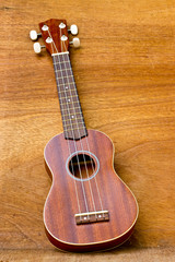 The ukulele is placed on a wooden floor.