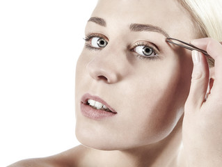 Junge Frau zupft Augenbrauen