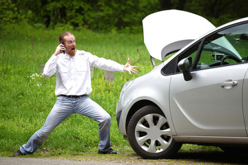 Driver furious with mobile phone a broken car by the road