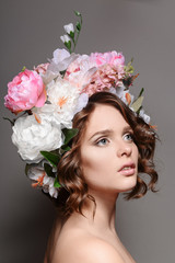 Beauty portrait of a girl with flowers in her hair on a gray bac