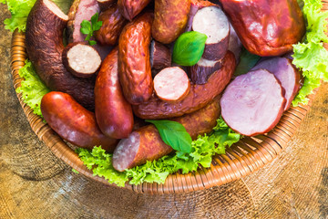 Various meat sausage basket wooden table background