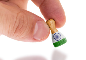 Hand holding wooden pawn, flag painting, selective focus