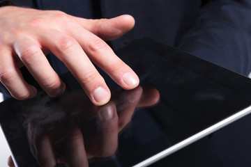 business man's fingers on tablet