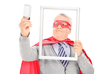 Mature superhero taking a selfie with picture frame