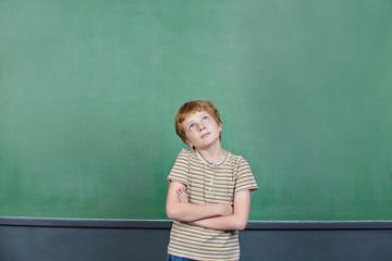 Kind beim Nachdenken vor Tafel