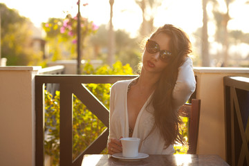 Obraz Cute young brunette resting with cup of coffee - fototapety do salonu