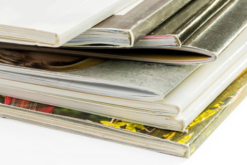 A pile of different catalogs on white background