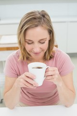 Eelaxed young woman having coffee in kitchen