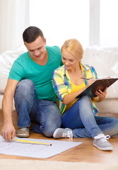 smiling couple looking at bluepring in new home