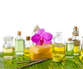 spa supplies with frangipani,oil,yellow candle on banana leaf