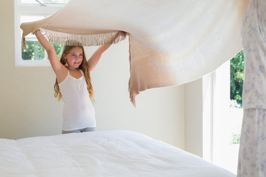 Girl making bed with mother