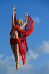 Beautiful blonde girl inred dancing with clouds on air