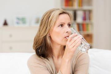 frau tinkt ein glas wasser zu hause
