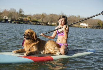 A child and a retriever dog on a paddleboard on the water.
