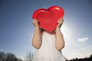 A child holding a red heart shape.