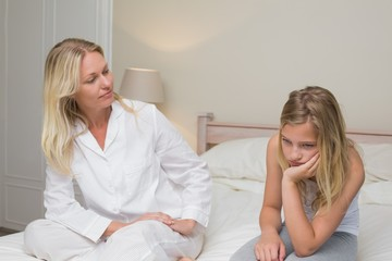 Woman looking at sad girl sitting on bed