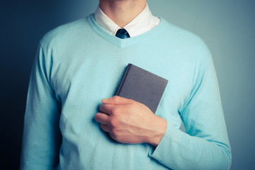Young man clutching small notebook
