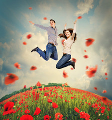 Happy young couple jumping in poppies field