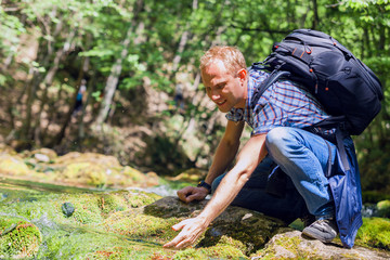 Traveler wash up with cool water from forest brook