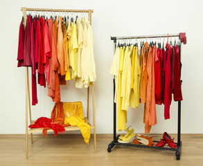 Color coordinated yellow, orange, red clothes hanging on a rack.