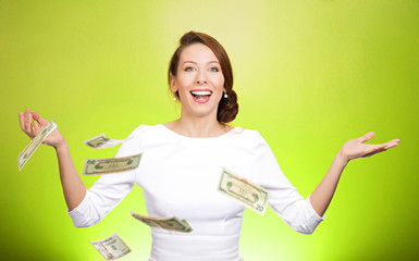 Money thrown in the air by excited woman on green background